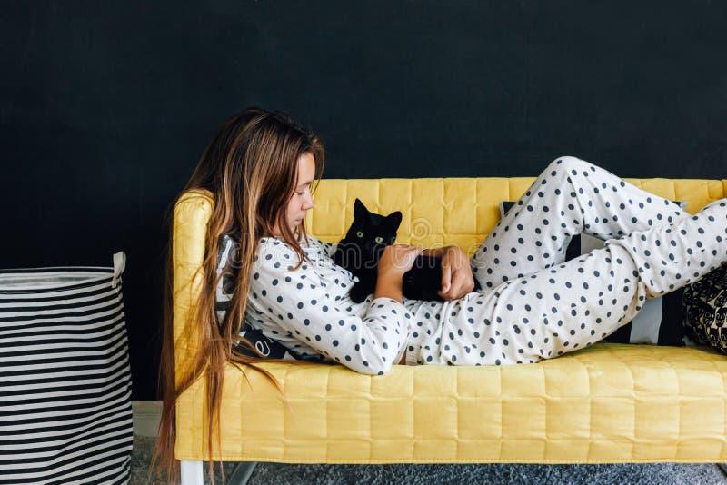 Niño pre adolescente en el sofá contra la pared negra en la vida moderna fotografía de archivo libre de regalías