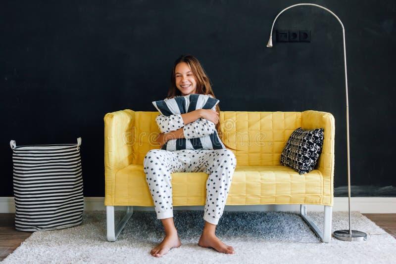 Niño pre adolescente en el sofá contra la pared negra en la vida moderna foto de archivo libre de regalías