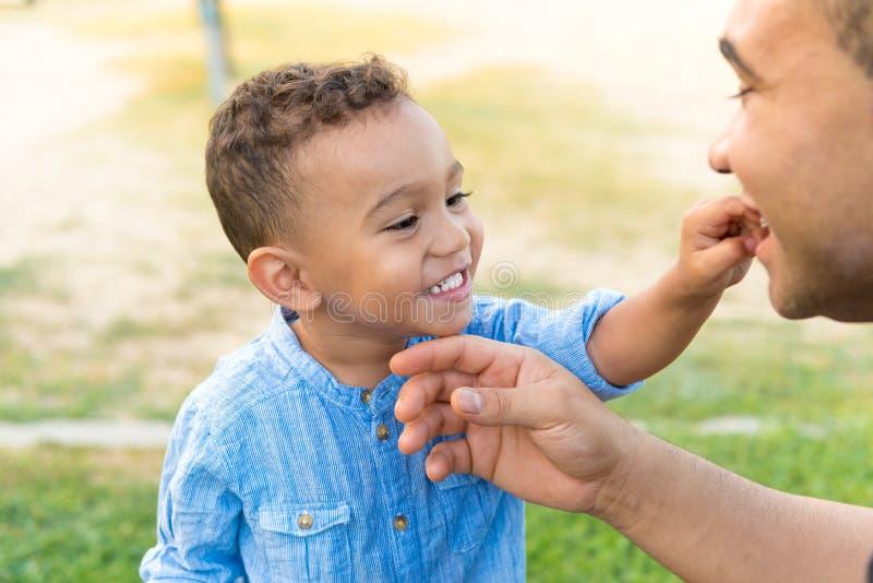 Niño precioso que muestra los dientes a su padre imagen de archivo