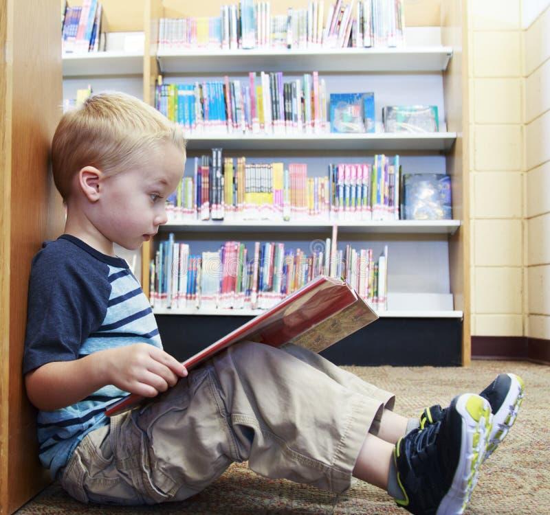 Niño preescolar que lee un libro en la biblioteca imagen de archivo