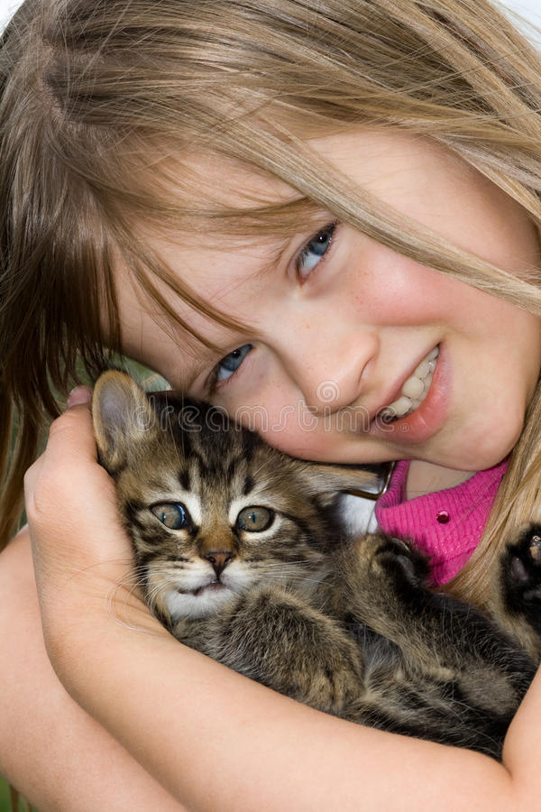 Niño que abraza un gatito. imagenes de archivo