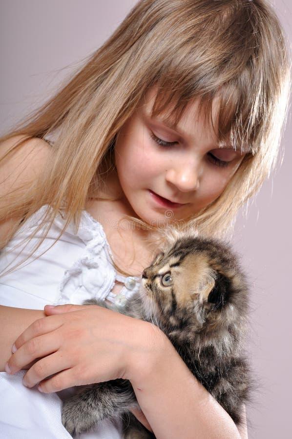 Niño que abraza un gatito imagenes de archivo