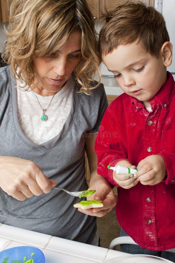 Niño que adorna las galletas con la mama foto de archivo