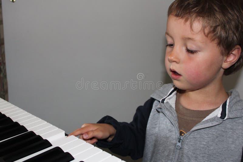 Niño que aprende jugar el piano fotos de archivo libres de regalías