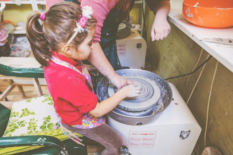 Niño que aprende nueva destreza en el taller de la cerámica foto de archivo