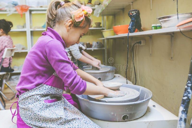 Niño que aprende nueva destreza en el taller de la cerámica fotografía de archivo