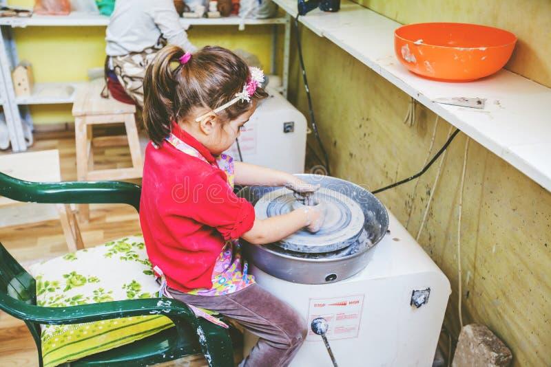 Niño que aprende nueva destreza en el taller de la cerámica imagenes de archivo