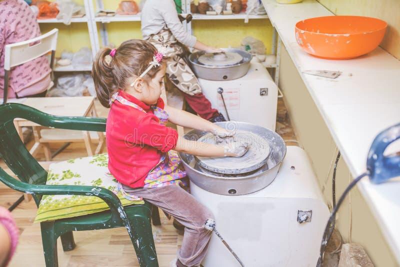 Niño que aprende nueva destreza en el taller de la cerámica fotos de archivo