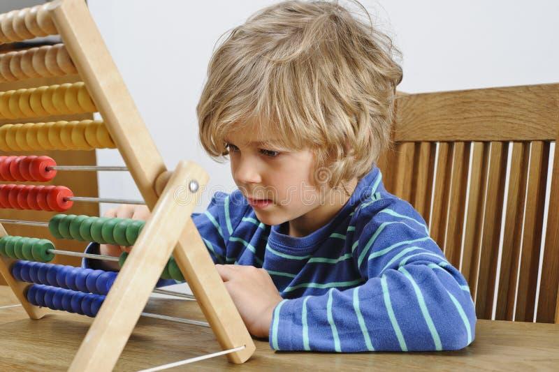 Niño que aprende utilizar un ábaco fotografía de archivo libre de regalías