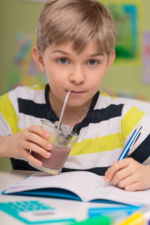Niño que bebe el cacao calórico fotos de archivo