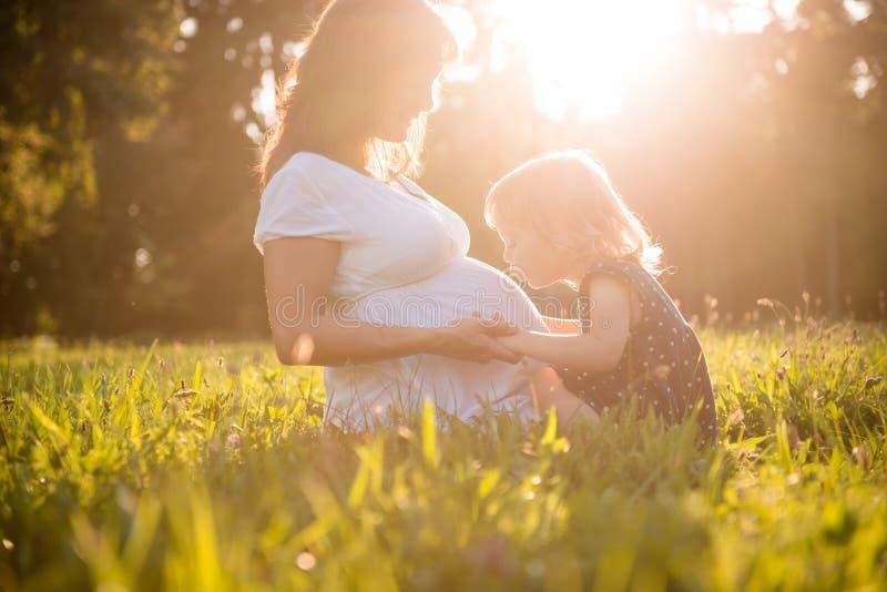 Niño que besa a la madre embarazada del og del vientre imagen de archivo