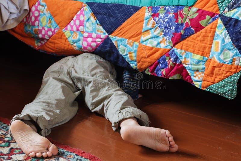 Niño que busca algo debajo de la cama fotos de archivo