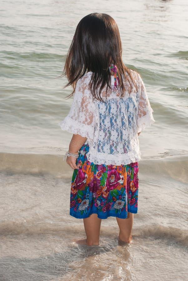 Niño que camina feliz en el mar imagen de archivo