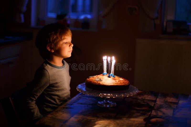 Niño que celebra su cumpleaños y que sopla velas en homem foto de archivo libre de regalías