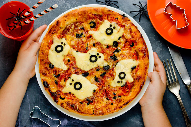 Niño que cocina la pizza en Halloween Pizza divertida del fantasma con la salchicha foto de archivo
