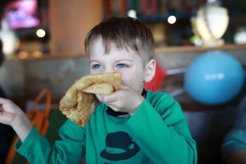 Niño que come el cheburek imágenes de archivo libres de regalías