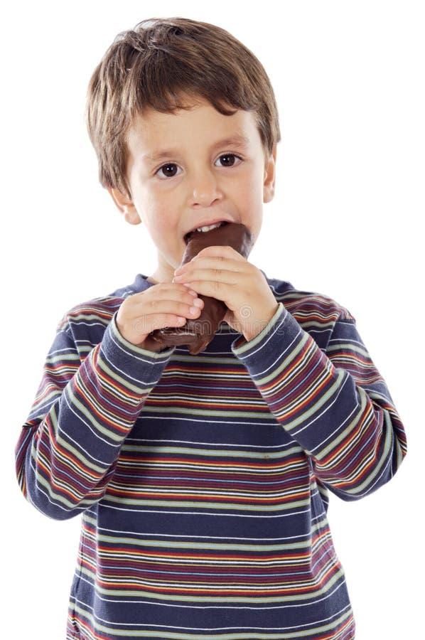 Niño que come el chocolate imagen de archivo