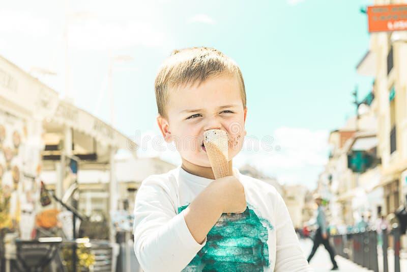 Niño que come el helado en la calle imagenes de archivo