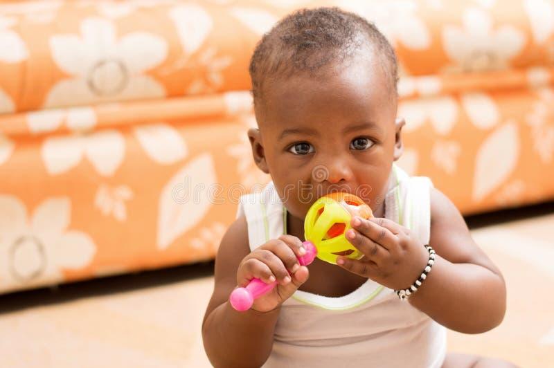 Niño que come el juguete imagen de archivo