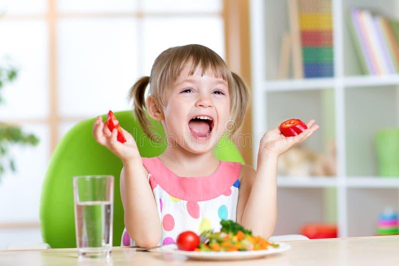 Niño que come la comida sana de las verduras en casa o fotografía de archivo libre de regalías