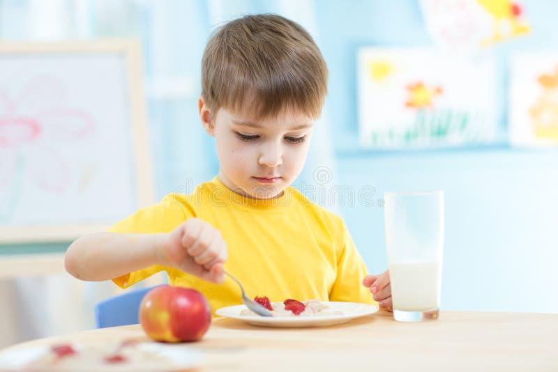 Niño que come la comida sana en casa fotografía de archivo