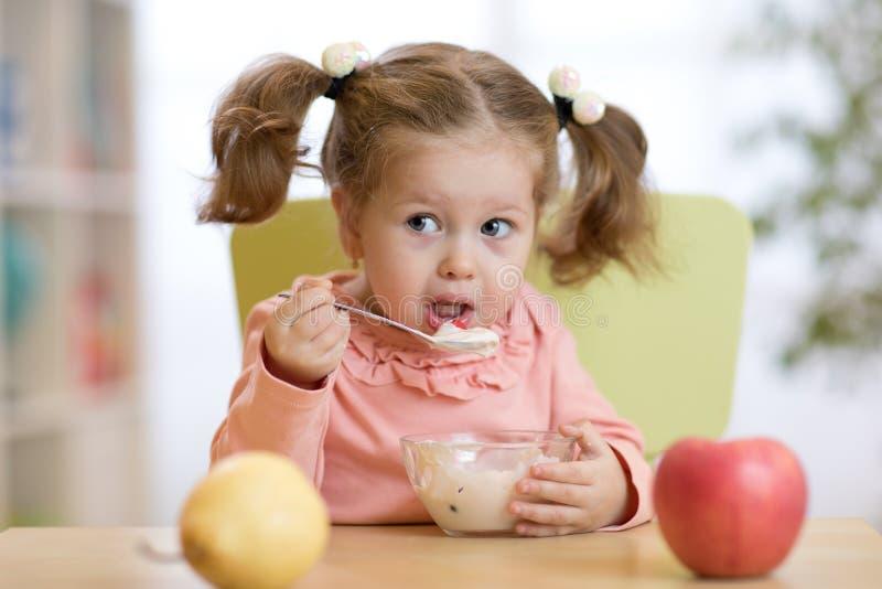 Niño que come la comida sana en casa o la guardería imagen de archivo