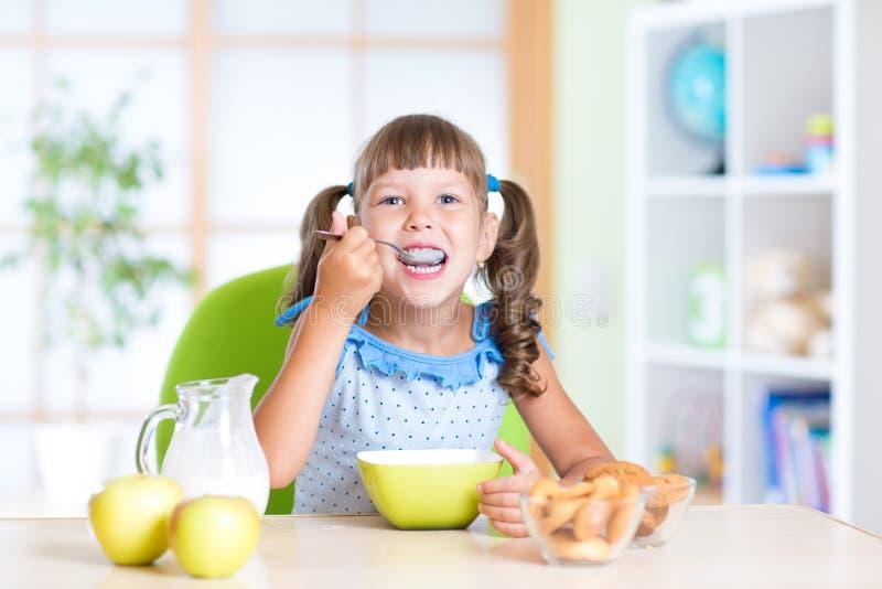 Niño que come la comida sana en cuarto de niños imágenes de archivo libres de regalías