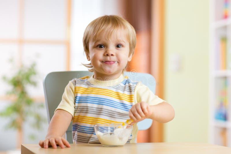 Niño que come la comida sana en el sitio del cuarto de niños fotografía de archivo libre de regalías
