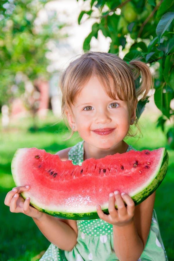Niño que come la sandía en el parque en tiempo de verano goce Retrato Muchacha feliz foto de archivo