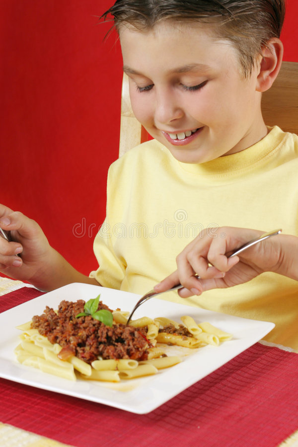 Niño que come las pastas imagen de archivo libre de regalías