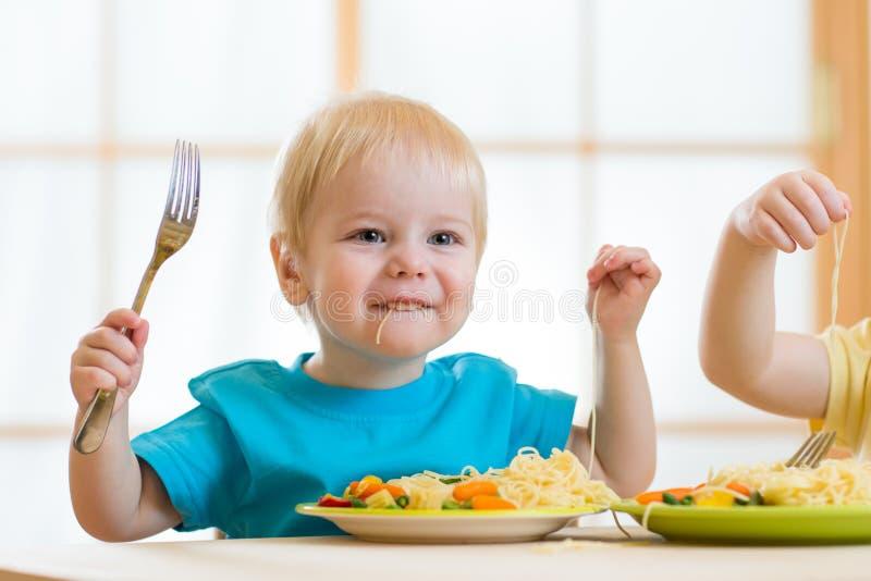 Niño que come los espaguetis con las verduras en cuarto de niños fotografía de archivo