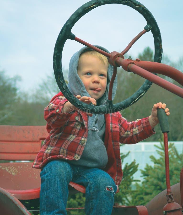 Niño que conduce el tractor imagenes de archivo