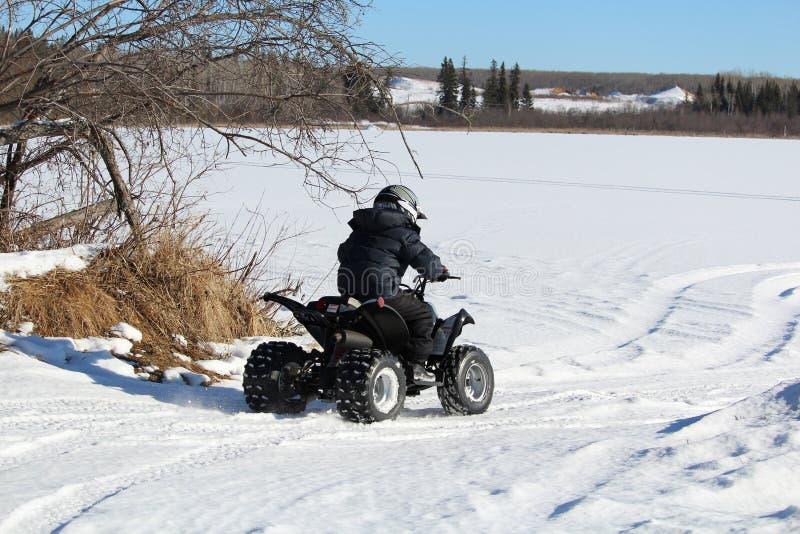 Niño que conduce su patio sobre un lago congelado fotografía de archivo libre de regalías
