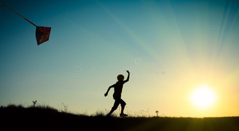 Niño que corre con una cometa imagen de archivo libre de regalías