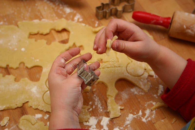 Niño que corta las galletas fotografía de archivo