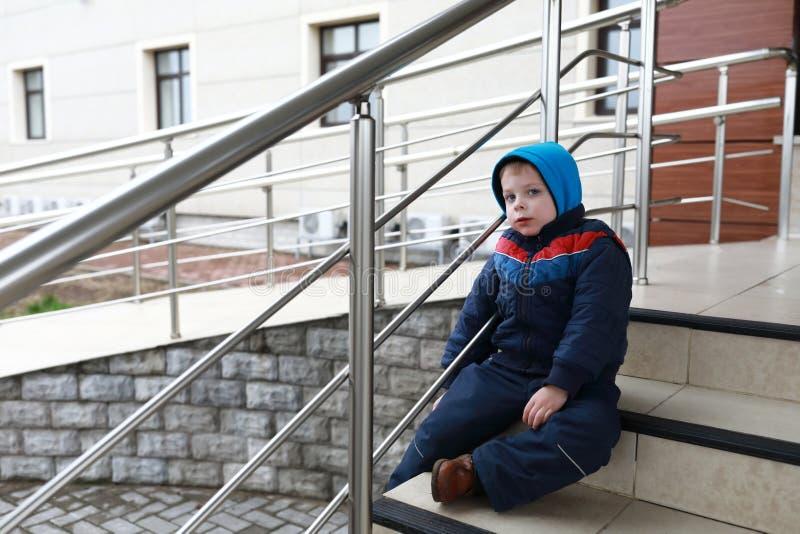 Niño que descansa sobre las escaleras fotos de archivo