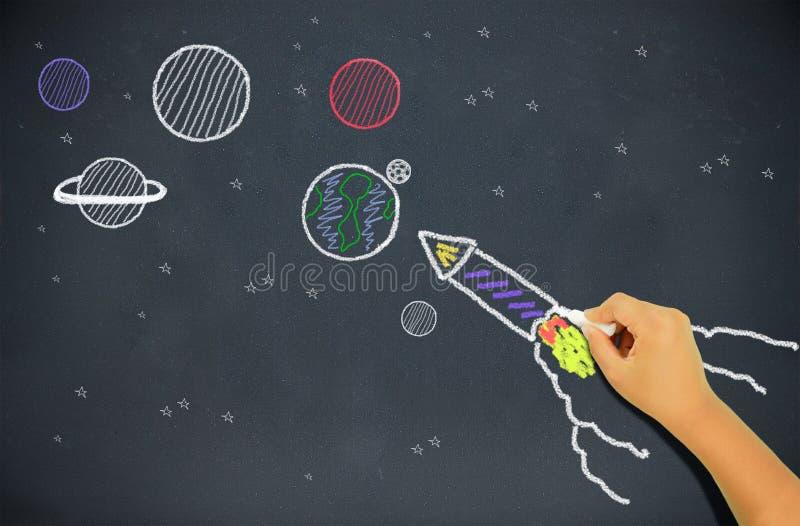 Niño que dibuja un cohete imagenes de archivo