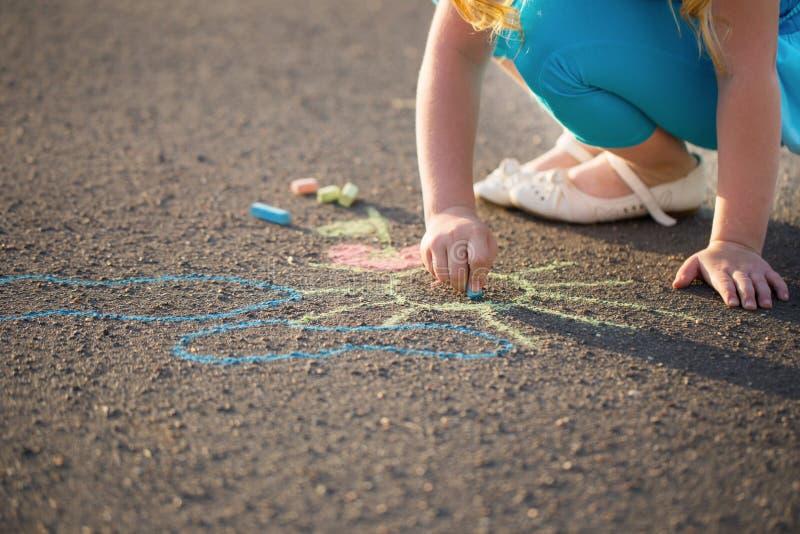 Niño que dibuja una tiza en el asfalto fotos de archivo libres de regalías