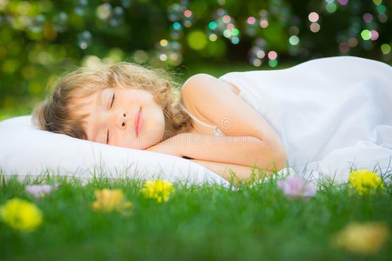 Niño que duerme en jardín de la primavera fotografía de archivo