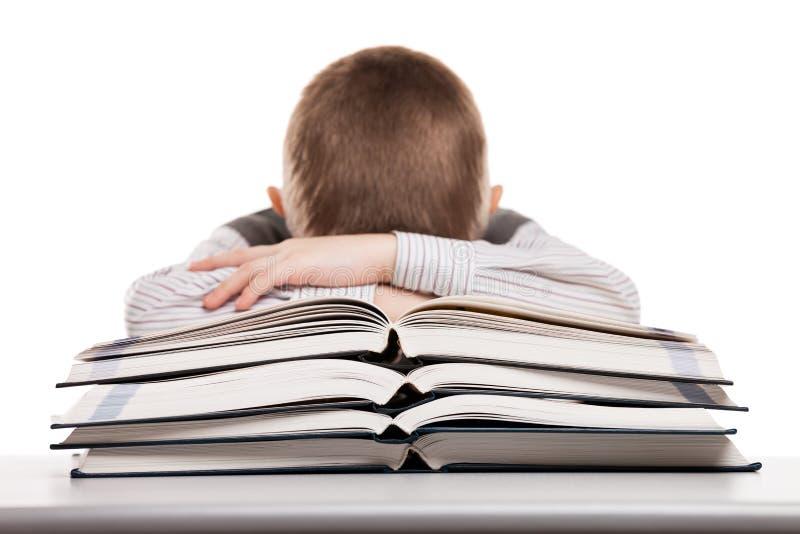 Niño que duerme en los libros de lectura imagenes de archivo