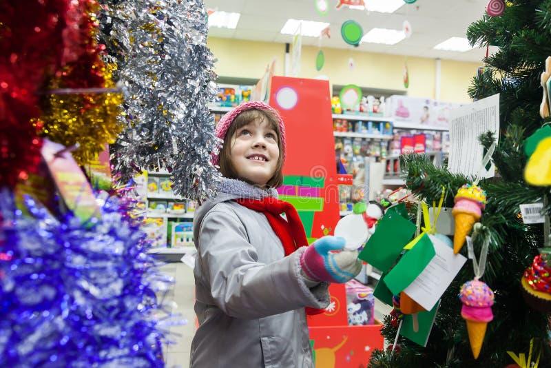 Niño que elige los juguetes para el árbol de navidad en tienda imagenes de archivo