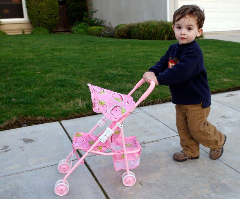 Niño que empuja el cochecito de niño fotografía de archivo