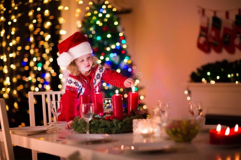 Niño que enciende una vela en la cena de la Navidad imagenes de archivo