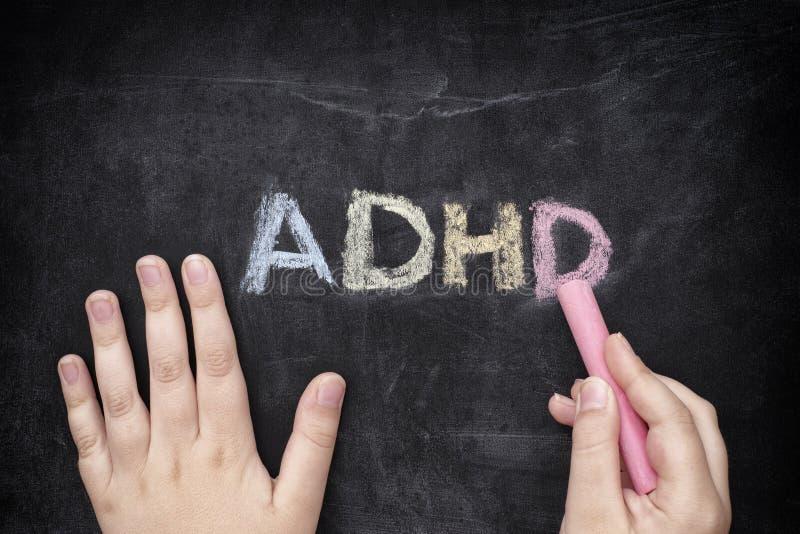 Niño que escribe ADHD en la pizarra imagenes de archivo