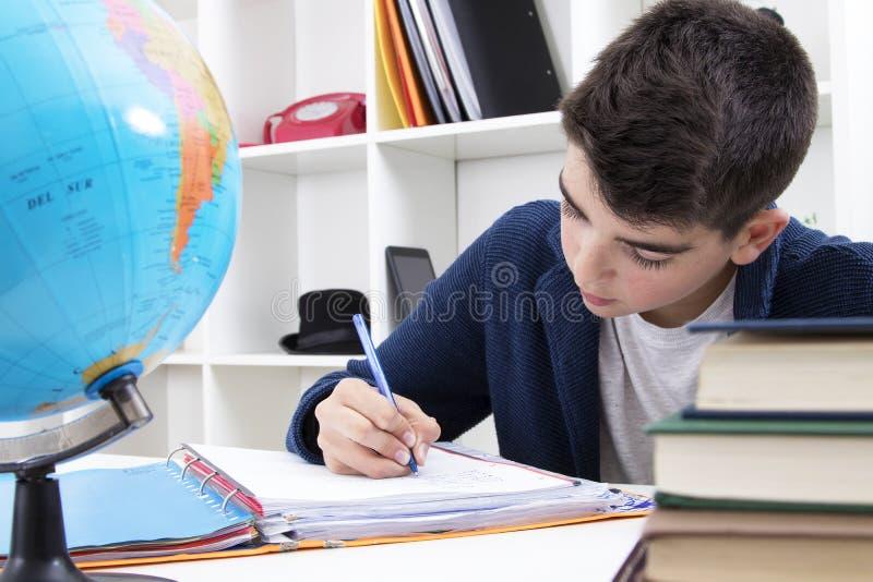 Niño que estudia y que escribe foto de archivo