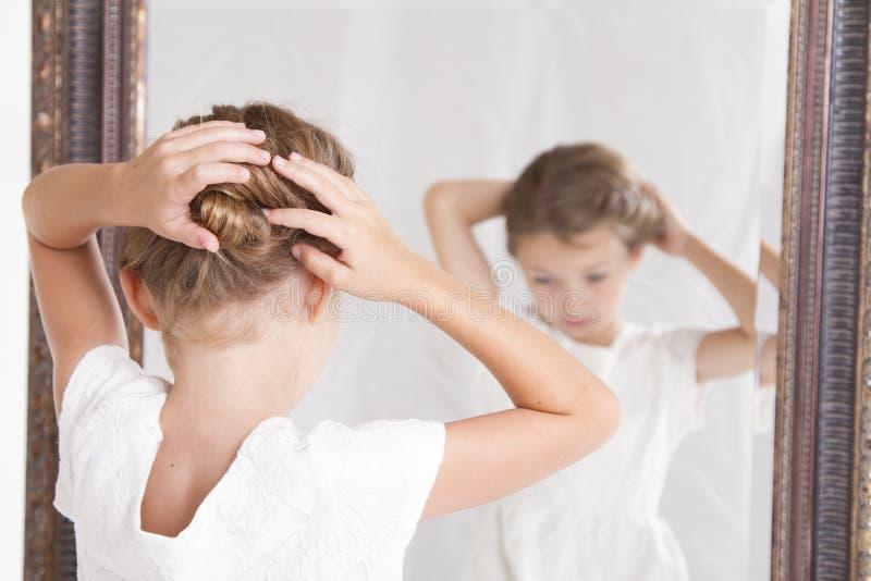 Niño que fija su pelo mientras que mira en el espejo fotos de archivo