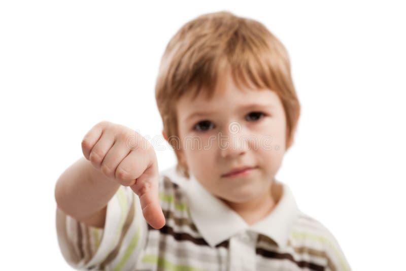 Niño que gesticula el pulgar abajo fotografía de archivo
