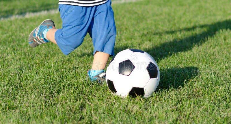Niño que golpea un balón de fútbol con el pie foto de archivo libre de regalías