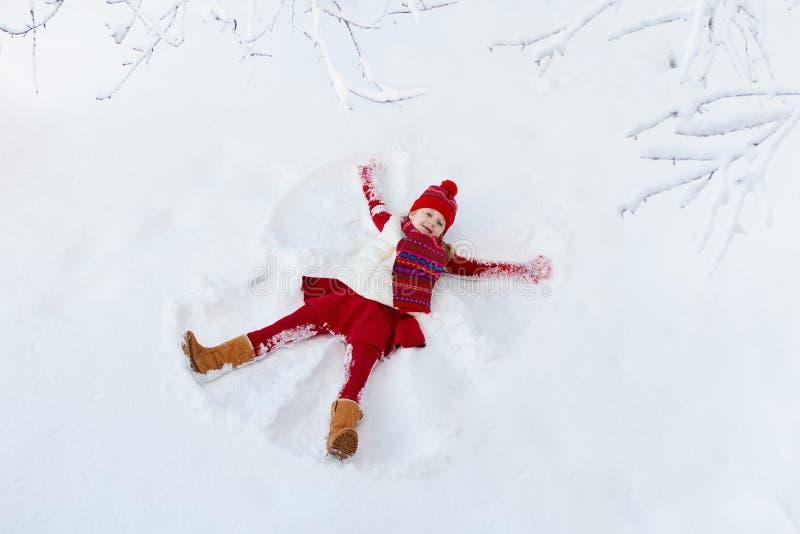 Niño que hace ángel de la nieve Diversión al aire libre del invierno de los niños imagen de archivo libre de regalías