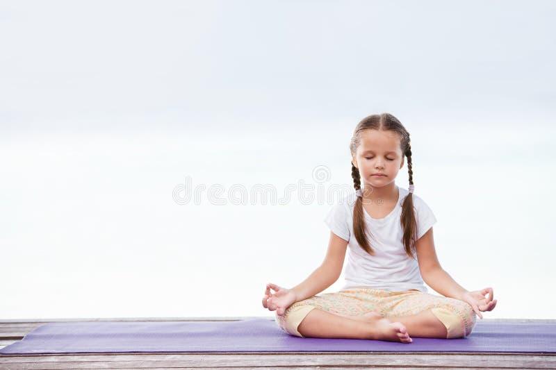 Niño que hace ejercicio en la plataforma al aire libre Forma de vida sana Muchacha de la yoga foto de archivo libre de regalías